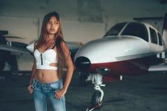 Härlig kvinnlig stående i flygplanhangaren, med modern ai Royaltyfria Bilder