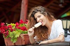 Härlig kvinnlig stående med långt brunt hår som äter glass nära en kruka med utomhus- röda blommor Attraktiv kvinna Arkivfoton
