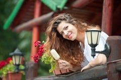 Härlig kvinnlig stående med långt brunt hår som äter glass nära en kruka med utomhus- röda blommor Attraktiv kvinna Royaltyfri Bild