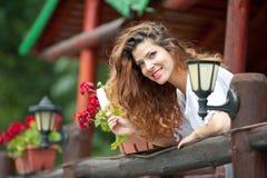 Härlig kvinnlig stående med långt brunt hår som äter glass nära en kruka med utomhus- röda blommor Attraktiv kvinna Arkivfoto