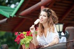 Härlig kvinnlig stående med långt brunt hår som äter glass nära en kruka med utomhus- röda blommor Attraktiv kvinna Fotografering för Bildbyråer