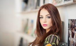 Härlig kvinnlig stående med långt rött hår mot en vägg med foto Äkta naturlig rödhårig man med inomhus långt hår arkivfoto