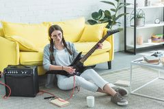 härlig kvinnlig tonårig gitarrist som spelar den elektriska gitarren på golv royaltyfri foto