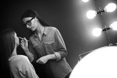 Härlig kvinnlig visagiste som koncentrerar på hennes jobb Arkivfoto