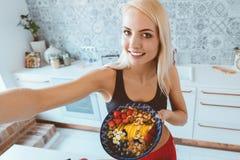 Härlig kvinnlig vlogger som rymmer den sunda frukostbunken och taki royaltyfria foton