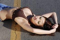 härlig läggande vägkvinna Arkivfoton
