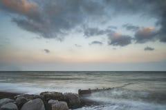 Härlig lång bild för exponeringssolnedgånglandskap av pir på havet in Arkivfoto