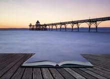 Härlig lång exponeringssolnedgång över havet med pirkontur c Arkivbild