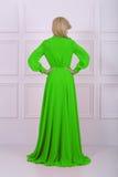 Härlig lång haired kvinna i grön klänning arkivbilder