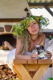 Härlig lång-vit hårkvinna i den vita klänning- och blommakransen som ligger på en träbänk med den gulliga fluffiga katten i gård  royaltyfri bild
