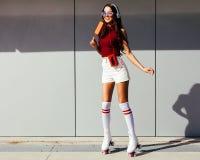 Härlig långbent asiatisk flicka som åker skridskor i rullskridskor och tycker om en glass på en sommardag Royaltyfria Bilder