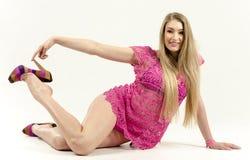 Härlig långhårig blondin i en rosa klänning som står frodigt flirty lyfta för kjol royaltyfri foto