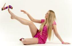 Härlig långhårig blondin i en rosa klänning som står frodigt flirty lyfta för kjol arkivfoton