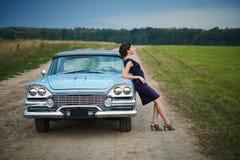 Härlig lady som plattforer nära den retro bilen royaltyfri fotografi