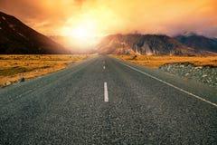 Härlig landscape av asfalthuvudvägperspektivet till soluppsättningen Royaltyfria Bilder