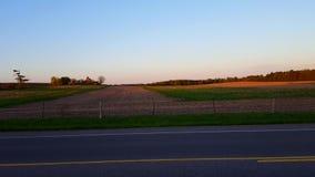 Härlig lantlig jordbruksmark på solnedgången med kamerapannan Scenisk bygdlantgård på skymning lager videofilmer