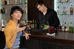 Härlig latinamerikansk kvinna som dricker på stången royaltyfri fotografi