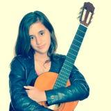Härlig latinamerikansk tonårs- flicka som kramar hennes akustiska gitarr Fotografering för Bildbyråer