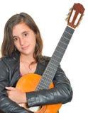 Härlig latinamerikansk tonårs- flicka som kramar hennes akustiska gitarr Arkivfoton