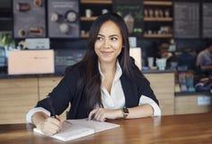 Härlig latinamerikansk ung kvinna i dräkten som arbetar i kafét royaltyfri foto