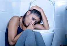 Härlig latinsk kvinna som sitter i badrummet som lider från anorexibulimia som känner desperat ledset och skyldigt i äta oordning arkivfoto