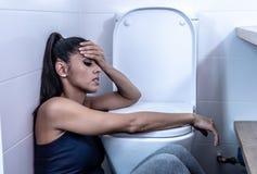 Härlig latinsk kvinna som sitter i badrummet som lider från anorexibulimia som känner desperat ledset och skyldigt i äta oordning royaltyfria foton