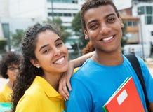 Härlig latinsk kvinnlig student med den indiska grabben på universitetsområdet av univ royaltyfri bild
