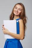 Härlig le affärskvinna, med dokument, på en grå färg tillbaka Fotografering för Bildbyråer