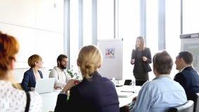 Härlig le affärskvinna som ger presentation till kollegor lager videofilmer