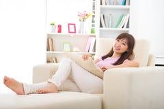 Härlig le asiatisk kvinna med minnestavladatoren. Ligga på sof Royaltyfri Foto