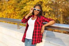 Härlig le bärande solglasögon för afrikansk kvinna, röd rutig skjorta i solig höst royaltyfri bild