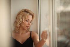 Härlig le blond kvinna med länge slanka ben som poserar sovrummet Royaltyfri Fotografi