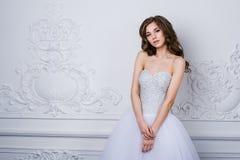 Härlig le brudkvinna med långt lockigt hår som poserar i bröllopsklänning på inre Inomhus stående för skönhet Arkivbilder