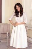 Härlig le brunettflicka i en vit brud- klänning Royaltyfria Foton