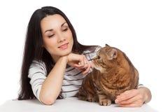 Härlig le brunettflicka och henne ljust rödbrun katt över vitba Arkivfoto
