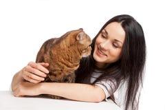 Härlig le brunettflicka och hennes ljust rödbrun katt över vita lodisar Fotografering för Bildbyråer