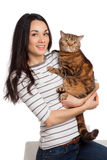 Härlig le brunettflicka och hennes ljust rödbrun katt över vita lodisar Royaltyfri Foto