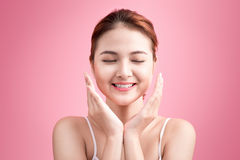 Härlig le flicka Ansikts- behandling Den unga asiatiska kvinnan med perfekt hud för rengöringen trycker på hennes framsida Fotografering för Bildbyråer