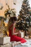 Härlig le flicka i aftondress nära trädet för nytt år och med gåvor Festlig frisyr och makeup Royaltyfri Bild