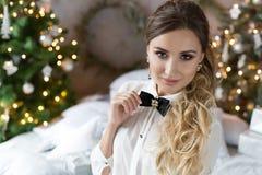 Härlig le flicka i aftondress nära trädet för nytt år och med gåvor Festlig frisyr och makeup Royaltyfri Foto