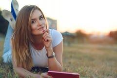 Härlig le flicka i den vita T-tröja och jeans som ligger i gräset på fältet och innehavet en flik i hennes hand Royaltyfri Bild