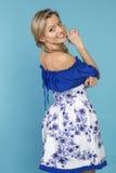 Härlig le flicka i en blå klänning Arkivfoto