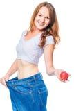 Härlig le flicka med ett äpple i hennes hand och stora jeans Fotografering för Bildbyråer