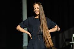 Härlig le flicka med långt rakt hår i svart klänning arkivfoto