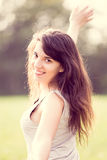 Härlig le flicka med långt svart hår i gardenlen som ler flickan med långt svart hår i trädgården Royaltyfri Foto