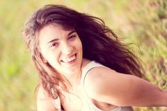 Härlig le flicka med långt svart hår i trädgården Royaltyfria Bilder