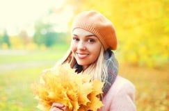 Härlig le kvinna för stående med gula lönnblad i varm solig höst arkivbild