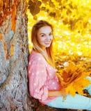 Härlig le kvinna för stående med gula lönnblad som sitter under träd i solig höst royaltyfria foton