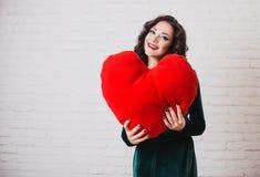 Härlig le kvinna med röda hjärtahänder på valentin dag Fotografering för Bildbyråer