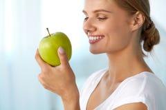 Härlig le kvinna med vita tänder som äter gröna Apple Arkivfoton